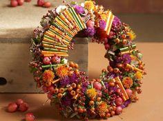 Kranz in leuchtenden Herbstfarben aus Blüten, Früchten und Band
