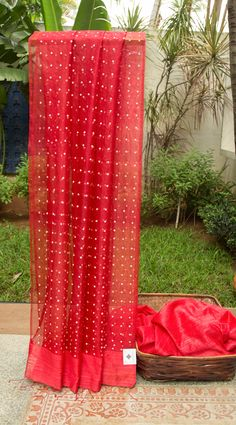 This striking Bailou sari has a beautiful texture on the body and pallu in ruby red kora with delicate white sequins woven all over where as the pleats are in deep apple red matka silk. The blouse…