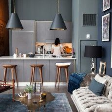 I love the palette and combination of furniture. I love the gray walls, the tufted couch, the wood chairs, the organic shaped table.