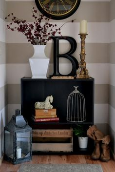 a great vignette on a black bookcase in front of a horizontal striped wall