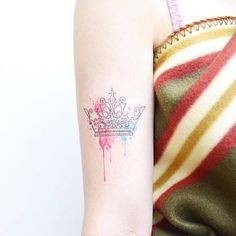 Fine line and watercolor crown tattoo on the right bicep.