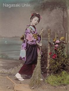 A girl wearing clogs sweeps the garden clean with a bamboo broom. A wooden dustpan is placed by her foot. A chrysanthemum fence stands to the right of the girl.  about 1890's by Ogawa,Kazumasa