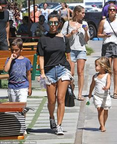 Casually chic: Kourtney flaunted her toned legs in trendy shredded shorts