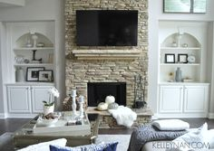 Built-ins on either side of fireplace | neutral living room fall decor | fur on hearth | stacked stone fireplace | tv over fireplace | bookshelf styling | how to style bookshelves