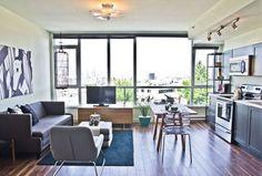 aménagement salon salle à manger - canapé gris graphite, tapis noir, meubles en bois et acrylique