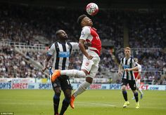Mbemba (left) stands his ground as Arsenal winger Oxlade-Chamberlain jumps up to win a hea...