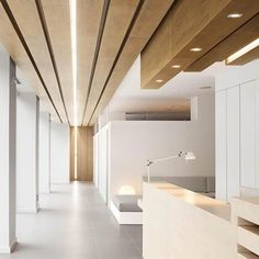 15 metre long wooden volumes fill the ceiling in this Barcelona dental clinic to represent a set of irregular teeth. Designed by @susannacotsinteriordesign with the complicity of two essential elements: an organic white palette, and light, both natural and artificial. #CernoInspiration