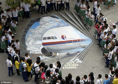Artists express hope: Students gather around a three dimensional artwork, based on the missing Malaysia Airlines flight MH370, that was painted on a school ground in Makati city. According to the artists, the artwork is their way of expressing sympathy towards the relatives of passengers onboard the missing Boeing 777-200ER