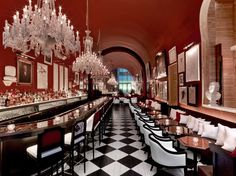 The second-floor bar, aptly named The Bar, draws inspiration from the American saloons of decades past and the royal stables at Versailles, from the natural-wood walls to the black-and-white checkerboard floors.