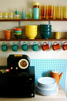 Vintage, colorful cups that all work together, pegboard, displayed glassware on open shelving. -B  love this kitchen. #home