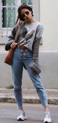 Musa do estilo: María Valdés. Cardigã cinza, t-shirt com estampa fun cinza, cinto caramelo com nozinho, mom jeans, tênis esportivo branco