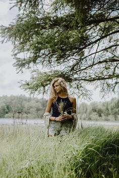 May 24, 2017 Outdoor photoshoot in grass. Holding flowers. In front of lake. Trees. by Joshua Schripsema.
