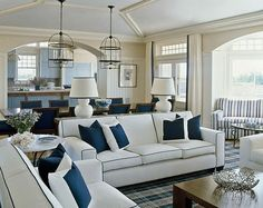 Crisp color palette of navy and white creates a traditional, Hampton beach style living room.
