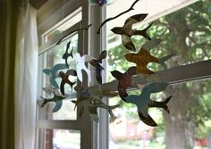 diy mobiles (birds or flowers) using magazine paper, a branch, and thread