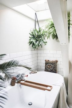 The plants in this bathroom add interest and create a nice use of colour in the otherwise plain but modern space.