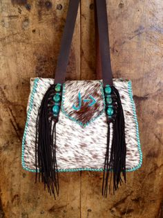 The cowhide Bonnie Bag with the recipients brand in turquoise suede, stitched with turquoise lace, and topped off with turquoise stones. From gowestdesigns.us
