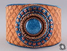 Linda Landy-USA   My first Beadsmith Inspiration Squad project. Bead embroidery using fish leather, O beads, Czech glass cabochon, True 2s, heavy metal seeds, Czech triangles, Miyuki rounds, Delicas, Beading Foundation, Fireline, E6000 and ultrasuede.