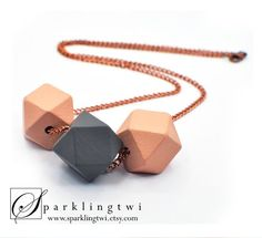 A minimalist geometric necklace. Made from hand painted wood beads in a lovely duo of grey and peach. Finished with a long copper chain, finished off with lobster clasp closure. The necklace is hand crafted and painted, the items are unique and may include slight variations in the wood texture and colour. It's a simple and modern piece for any jewelry collection. A great gift for her.