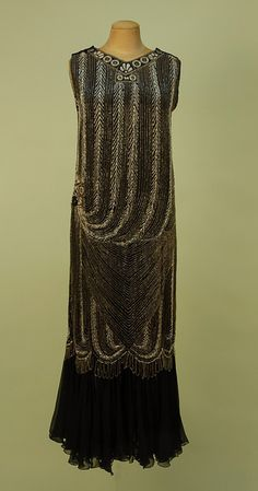 ART DECO BEADED BLACK SILK GEORGETTE GOWN, 1920's. Sleeveless column with V-neck and back in a chevron and stripe swag pattern of crystal, white and rhinestone beading with banded neckline and right hip medallions, looped scalloped fringe below knee over a gathered chiffon flounce. whitakerauction.com