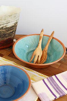 Olive wood salad servers and pottery serving bowls.