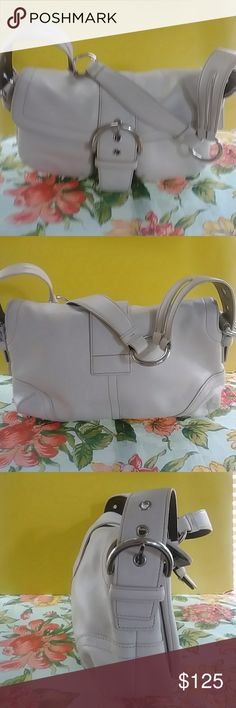 COACH * SOHO WHITE* SHOULDER BAG Beautiful Summer winter white Soho 2005 shoulder bag pristine condition in and out. No spots, stains or scuffs. No visible signs of wear. Silver hardware with lg magnetic buckle closure. 2 good size pockets under front flap. Full length zip pocket. And 2 slip pockets inside. Interior has divider inside separating w lg compartments. Very pretty shoulder bag. 12in wide x 8in tall, 3in depth.12in adj shoulder strap COACH Bags Shoulder Bags