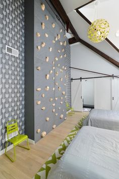This fun kid's room from Linc Thelen features white walls with lime accents and includes a rock-climbing wall, dual bunk beds, fun graphic wallpaper and creative rope sconce lights.