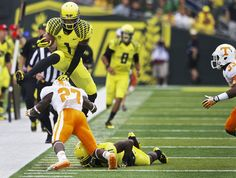Oregon Ducks wide receiver Josh Huff (1), hurdles Tennessee Volunteers defensive back Justin Coleman (27)
