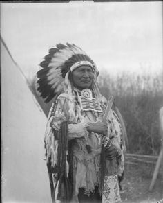 A portrait of Cuts The Bear's Ears, a Crow man, wearing a feather headdress. Collection Richard Throssel. Date Original: 1902-1933. University of Wyoming. American Heritage Center.