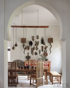 The dining chairs were inspired by Frank Lloyd Wright. A collection of African masks hangs on the wall, and a suzani from Uzbekistan. Dining room by Maryam Montague.