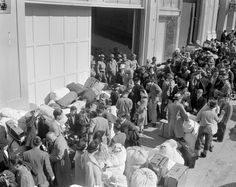 As military police stand guard, people of Japanese descent wait at a transport center in San Francisco April 6, 1942 for relocation to an internment center at Santa Anita racetrack near Los Angeles.