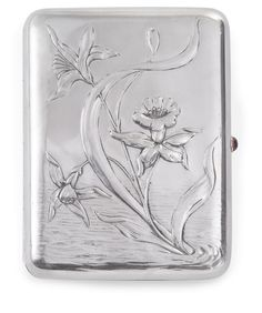 A Fabergé Silver Cigarette Case, Moscow, circa 1900, rectangular with rounded corners, the hinged cover chased and repoussé with daffodils and lilies in a rainy spring ground, with gold set red hardstone thumbpiece.