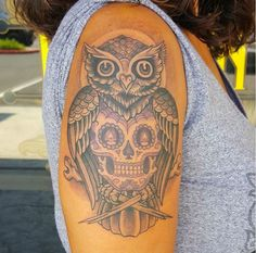 Sugar skull tattoo fused with an owl on the arm.