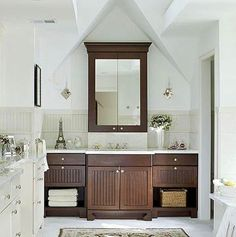 Mirrored doors on center stack...Here, the vanity is outlined by a dormer and illuminated by two skylights. A large mirror doubles as a medicine cabinet, and is stained to match the bathroom cabinets below. Make your vanity stand out by using bold contrasts, but be sure to extend some part of the surrounding color scheme to the vanity. In this bath, the dark-wood cabinetry is softened by a light countertop, ensuring that the vanity fits in with the rest of the bath.