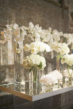 Varying height and flower centerpieces of same color pallette. (Doesn't have to be all white)