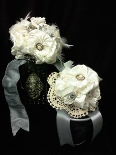Upcycled  bouquet....made from strips of fabric from the bride's mom's wedding dress (nobody was going to wear that 1990gem again!) and veil (great gobs of poofy illusion netting!) rolled into fabric flowers. Vintage brooches and buttons adorn the centers of the flowers along with momentos honoring the bride's grandmothers that have passed away- a tiny hummingbird charm for one and the spoon ring of the other.
