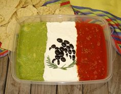 Mexican flag, guacamole, sour cream and salsa with black olice slices and herbs