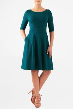 Soft cotton knit is pleated at the the boat neck and top-stitched at the princess seamed bodice, banded waist and flared skirt for an updated A-line dress.