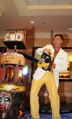 Bruce Campbell cutting the Evil Dead cake in the most appropriate way possible.