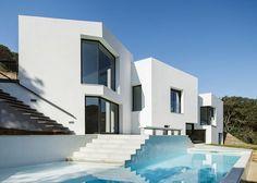 Casa minimalista em terreno inclinado. Morada dribla lote íngreme e ganha luz natural