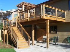 Deck with covered cooking area and wide stairway, with flagstone patio below.