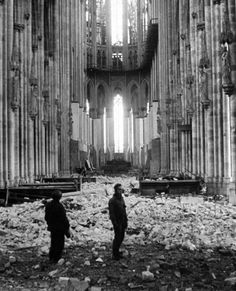 Soldiers wander through the bombed-out Cathedral of Cologne, 1945.