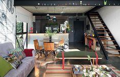 O estilo industrial, típico de lofts nova-iorquinos, foi reforçado pelos acabamentos em tons de cinza e preto. Na viga de aço aparente do living, que sustenta o mezanino, o morador expõe a coleção de toy art. Projeto da arquiteta Bruna Riscali