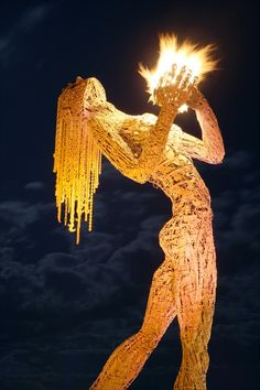 Woman holding fire sculpture at Burning Man. Incredible works of art that are burned at the end of the festival