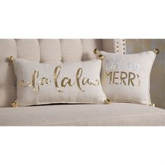 "2 styles. White burlap pillows with piped edges and gold jingle bells at corners feature 'fa la la"" and 'Oh so MERRY' sentiments in gold or silver and gold sequins."