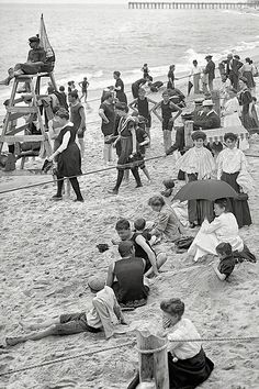 An American Gilded Age view of the Jersey Shore - New Jersey, c.1905. Photograph includes; sunbathers on the sand, lifeguard on stand, ladies & men's modest wool swimming suits, also ladies, gentlemen, and childen wearing full street attire, and a lady holding an umbrella for shade from the sun. ~ {cwlyons} ~ (Image: librar-y tumblr)