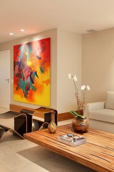 The modern end tables and colorful mural provide a distinctive look for this living room