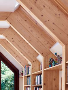Bookshelves and skylights are slotted into spaces between timber ribs in this West London house extension.