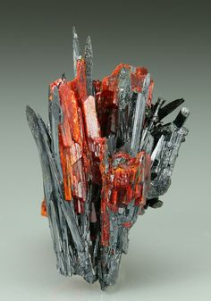STIBNITE with REALGAR Minerals from Baia Sprie, Maramures Co, Romania Spiky terminated prismatic crystals of metallic dark grey Stibnite form two inter grown open divergent clusters. Grown between the crystals of Stibnite are orange to red blocky crystals