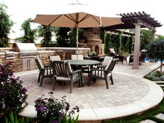 12 Amazing Outdoor Kitchens: Plenty of stacked stone, vine-covered columns and a circular cobblestone patio give this space a lovely Tuscan flair.  From DIYnetwork.com