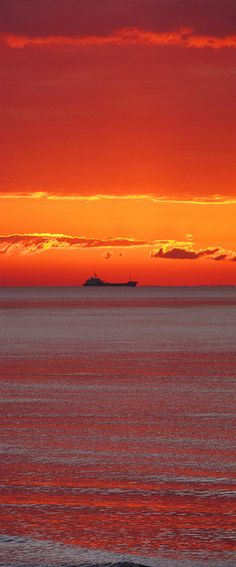 Tequila Sunrise - Dredger boat leaving Shoreham port at sunrise, England.